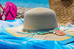 Hat and flip flops on the beach. Straw hat and flip flops on the beach stock images
