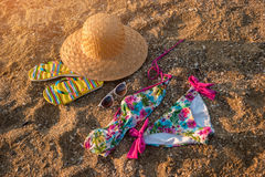 Hat and flip flops. Colorful swimsuit on sand. Be in style of summer. Get away from city bustle royalty free stock photography
