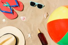 Hat, flip flops and shades and beach ball on sand royalty free stock photography