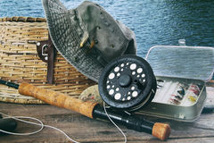 Hat and fly fishing gear on table near the water Royalty Free Stock Photo