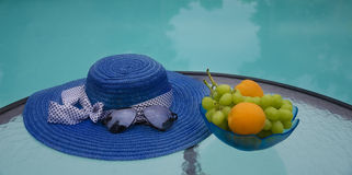 Hat and fruits by the swimmimg pool. Woman's hat, sunglasses and grape with apricots in glass plate are on table by the swimming pool Royalty Free Stock Photos