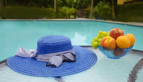 Hat and fruits by the swimmimg pool. Woman's hat, sunglasses and grape with peaches and apricots in glass plate are on table by the swimming pool Royalty Free Stock Photography