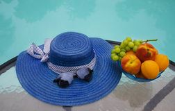 Hat and fruits by the swimmimg pool. Woman's hat, sunglasses and grape with peaches and apricots in glass plate are on table by the swimming pool Royalty Free Stock Images