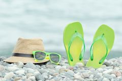 Hat, glasses and flip flops on the pebble beach. Sea in the back. Ground royalty free stock photo