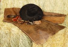 Hat, gloves and spurs. Hat, gloves, spurs and chaps resting on hay bales royalty free stock image