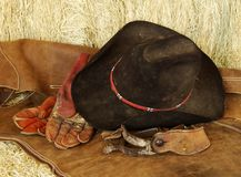Hat, gloves and spurs. Hat, gloves, spurs and chaps resting on hay bales royalty free stock images