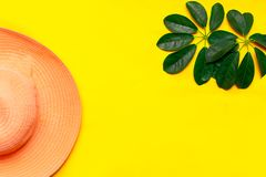 Hat and green leaf tropical flatlay on yellow color background, top view.  royalty free stock photo