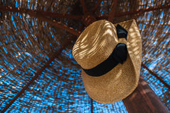 Hat hanging on a straw parasol Stock Photography