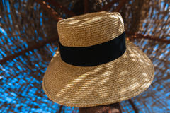 Hat hanging on a straw parasol Stock Photo