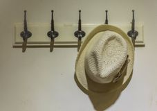 Hat hanging on the wall. A hat hanging on the old white wall Royalty Free Stock Photo