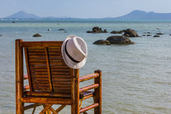 Hat hangs on a chair on the background of the sea Royalty Free Stock Photography