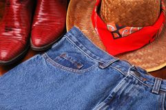 Hat Jeans & Boots. Blue Jeans & Cowboy Hat and Boots on dark wood floor stock image