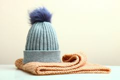 Hat and a knitted scarf. A beautiful gray hat with a pompon and a knitted scarf on a neutral background Royalty Free Stock Images