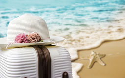 Hat on luggage at the beach Stock Images