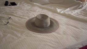 The hat lying on the bed in hotel room. Unrecognizable woman sleeping in the background in a comfortable bed. Tourism
