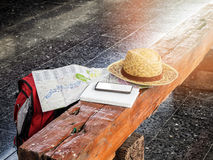 Hat, map, cellphone and notebook on bench at train station. Royalty Free Stock Photography