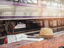 Hat and notebook on bench at train station Stock Image