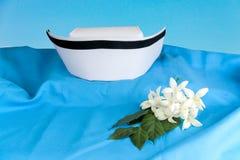 Hat nurse white and Millingtonia hortensis flowers. On blue fabric. symbol of nursing thailand and Thai traditional medicine stock photos