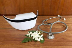 Hat nurse white and stethoscope. Hat nurse white and Millingtonia hortensis flowers and stethoscope on wood table. symbol of nursing thailand and Thai stock images