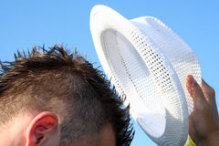 Hat off. Picture of man taking of a white summer hat Stock Photo