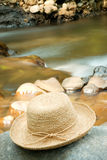Hat On Rocks By River Stock Photo