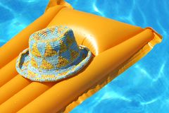 Hat on orange airbed Royalty Free Stock Images