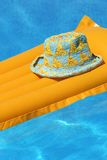 Hat on orange airbed. Floating in swimming pool royalty free stock photo