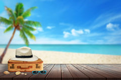 Hat, passenger suitcase, sunglasses, shell on beach table. Royalty Free Stock Photo