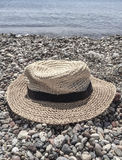 Hat on a pebbly beach. A straw hat on a pebbly beach in summer Stock Photos