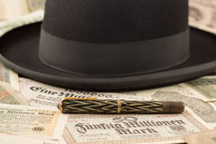 Hat and pen. Black hat and a pen on lots of money Royalty Free Stock Photos