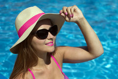 With hat at poolside. Attractive smiling woman with hat and sunglusses at poolside Stock Photography