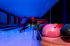 Hat rosa Bowlingkugeln bereites zum Spieler zu werfendem Ball auf Th Lizenzfreie Stockfotografie
