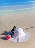 Hat and rose in waves on a beach Royalty Free Stock Images