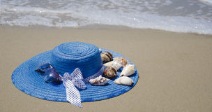 Hat on a sand. Blue summer woman's hat with seashells on beach's sand Royalty Free Stock Photography