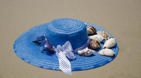 Hat on a sand. Blue summer woman's hat with seashells on beach's sand Stock Photography
