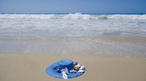 Hat on a sand. Blue woman's summer hat with seashells on a sand by the ocean Stock Photography