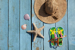 Hat, sandals, seashells and starfish on the blue background. Hat, sandals, seashells and starfish on the blue wooden background Royalty Free Stock Image