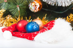 Hat of Santa Claus and Christmas balls. Hat of Santa Claus and balls on Christmas tree background Stock Photography
