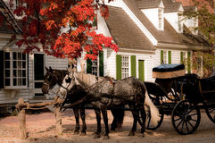 At The Hat Shop. A horse drawn carriage parked outside the hat shop in a colonial village setting Stock Images