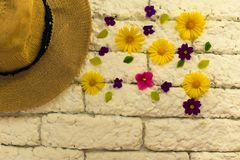 Hat and small wild flowers on a white brick wall Hello Summer. Hat and small wild flowers on a white brick wall royalty free stock photos