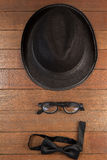 Hat, spectacles and bow tie arranged on wooden background Stock Photography