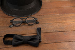 Hat, spectacles and bow tie arranged on wooden background Stock Photos