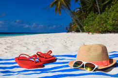 Hat, sun glasses and flip flops on a tropical beach. Vacation concept royalty free stock photography