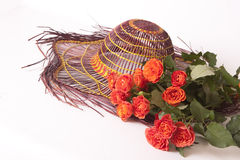 Hat from the sun and orange roses Royalty Free Stock Image