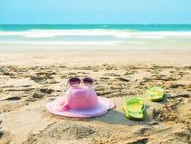 Hat , sunglass, flip flop on sand beach Stock Photos