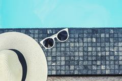 Hat and sunglass on luxury swimming pool tropical beach resort , summer concept.  royalty free stock images
