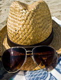 Hat, sunglasses and towel on the beach, holiday co Stock Photography