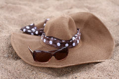 Hat and sunglasses on a beach Stock Image