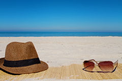 Hat and sunglasses on a beach in summer Royalty Free Stock Image