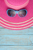 Hat and sunglasses on blue wood background.Summer holiday back Stock Images